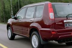 Tumši sarkana Nissan X-Trail aizmugure